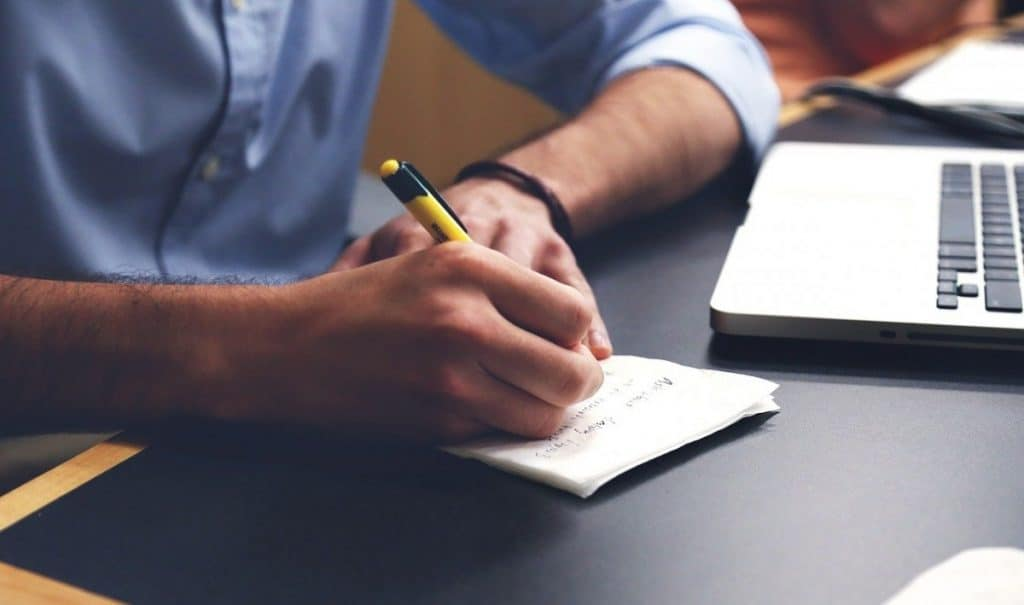 writer writing in notebook